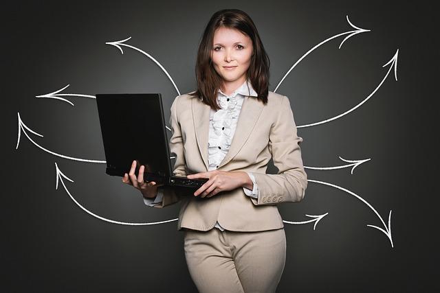 Frau mit Notebook vor Tafel