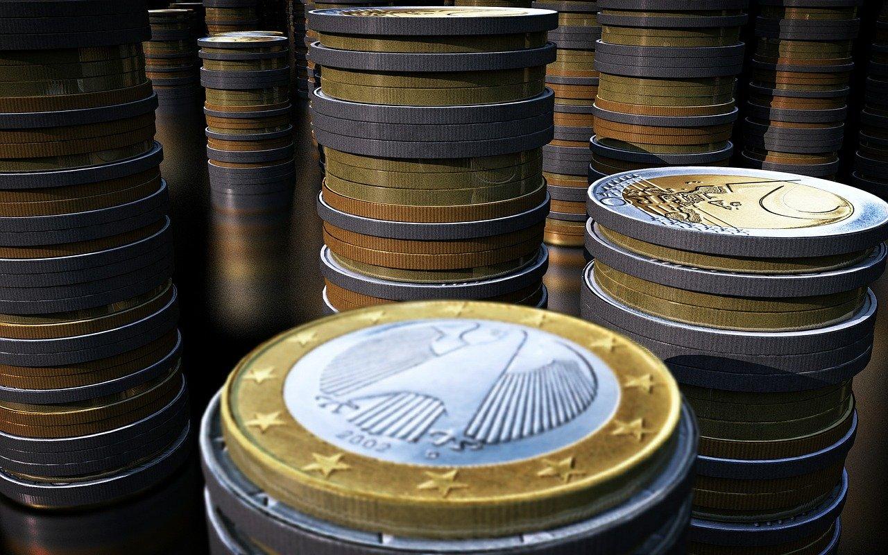 Münzen auf Geldscheinen mit Kugelschreiber und Brille