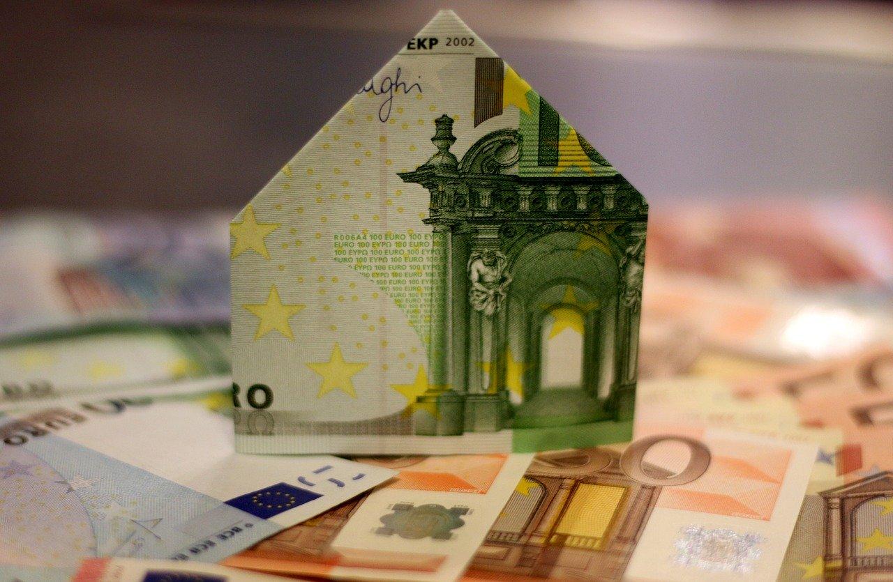 Kleine Plastikhäuser auf Geldschein und Kaufvertrag